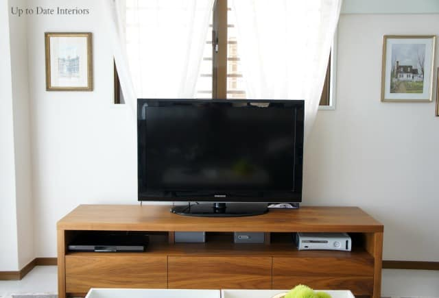 modern tv stand in bright living room with art on walls