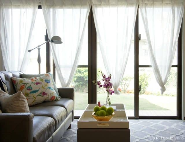 knotted curtains in a rental living room with lots of windows and grey leather sofa