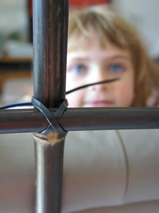 little girl looking at bamboo ladder
