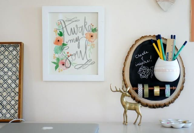 office wall with art and DIY organizer on a wood slice and white planter