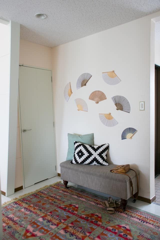 foyer with fans on the wall, rug, and upholstered bench