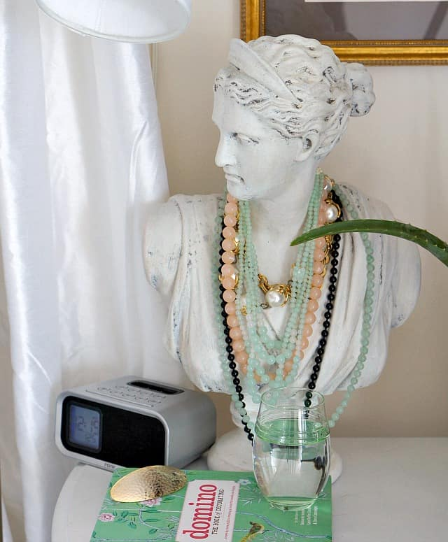 woman's bust with necklaces on bedside table with clock and book