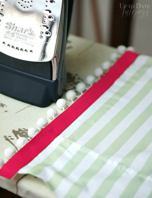 Attach strawberry ribbon to your candy stripe coverlet with iron on fusible tape.