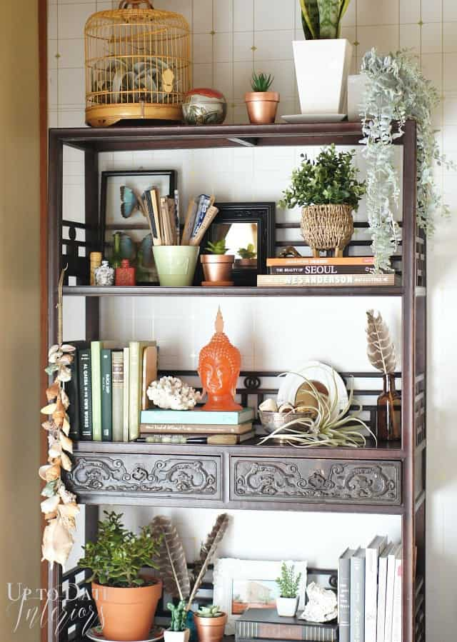 Mix copper pots, terra cotta, plants, books for a global eclectic bookcase