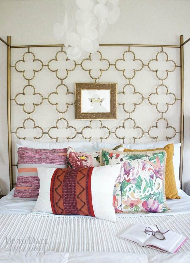 art hung on gold canopy bed for a focal point and global style with white bedding and colorful pillows