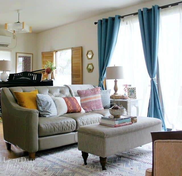 rental friendly decorating ideas for fall .Blue curtains on big window wood shutters on small window.  Piano behind grey leather sofa with grey ottoman coffee table
