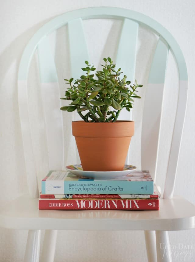 books on a white chair with a plant