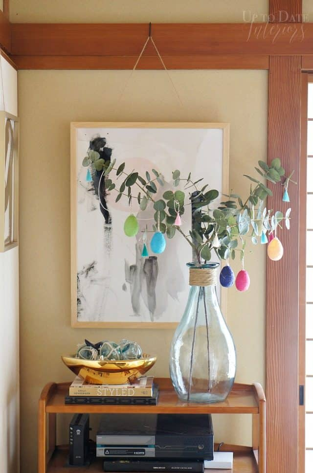 global eclectic spring and easter decor on a shelf with art and warm wood architecture