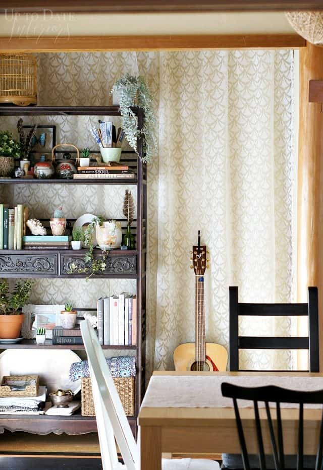 Corner of spring dining room home tour with asian wood eterge, lace curtain, and guitar