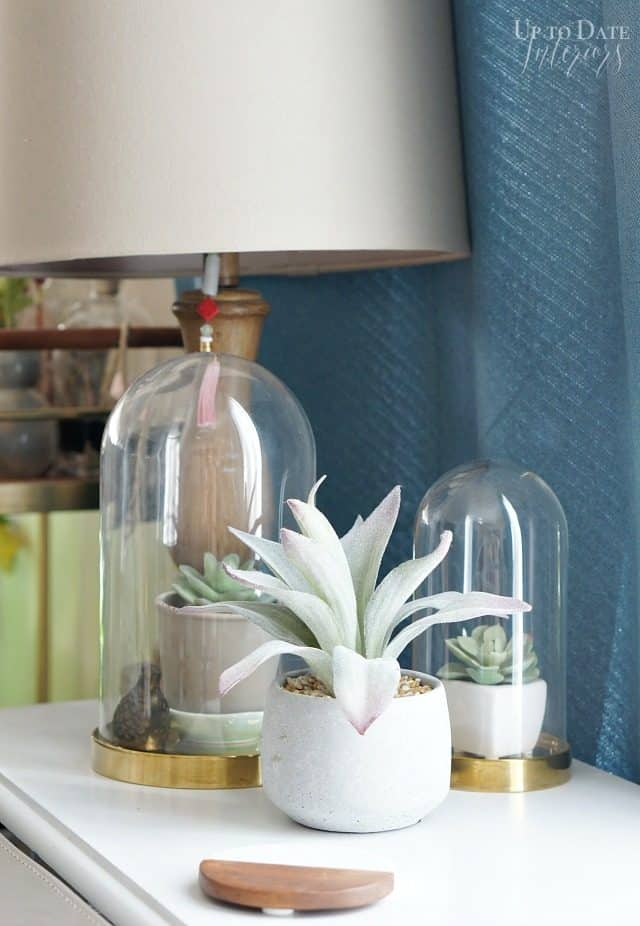 Faux plants on a side table with a lamp make for great Spring decor