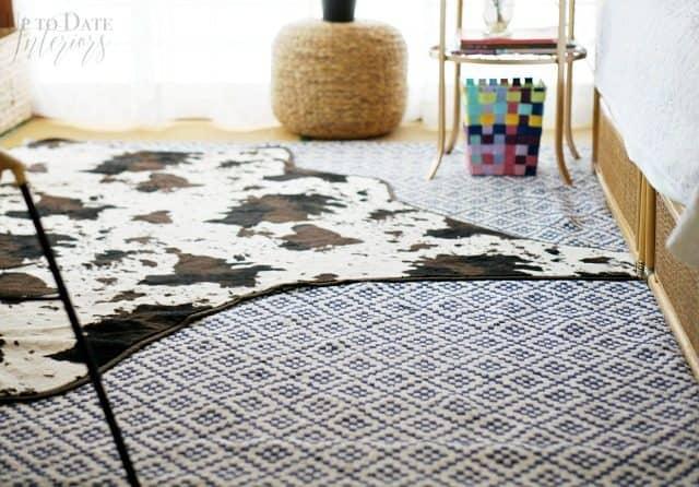 Layered cowhide rug over flatweave blue and white rug on top of tatami floor in Japanese bedroom