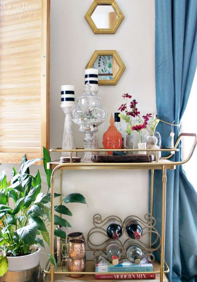 bar cart Spring decorating ideas with lots of color, large plant, mirrors, and windows