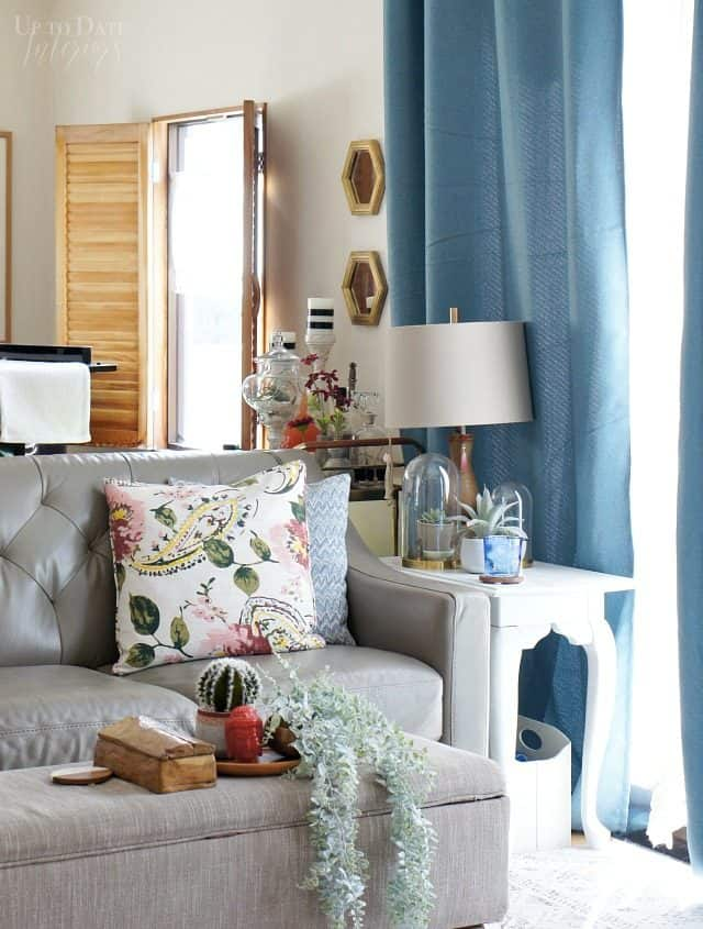 spring decorating ideas on a budget in the living room with sofa, ottoman, blue curtains, and a window with wood shutters