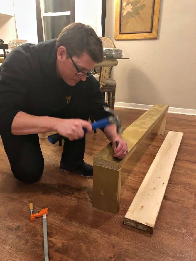 Chris Hammering Nail Into Gold Wood Base