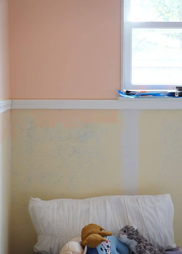 bedroom wall with chair rail, drywall patching, and window
