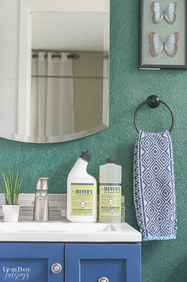 Green household cleaning products for the bathroom sitting on a blue vanity with a green wall.