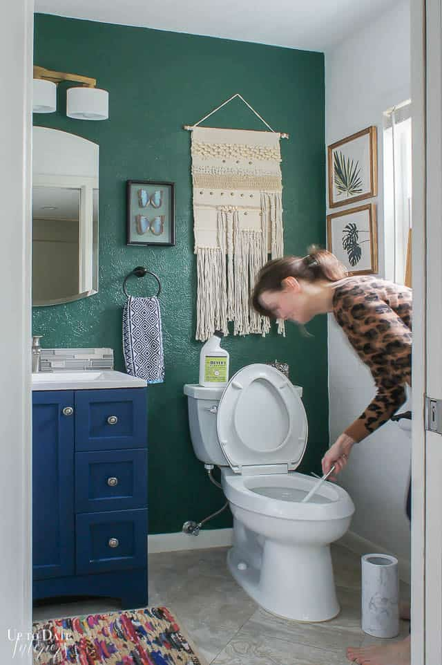 Best green cleaning products for your bathroom with a pretty boho green and blue bathroom and girl cleaning toilet.