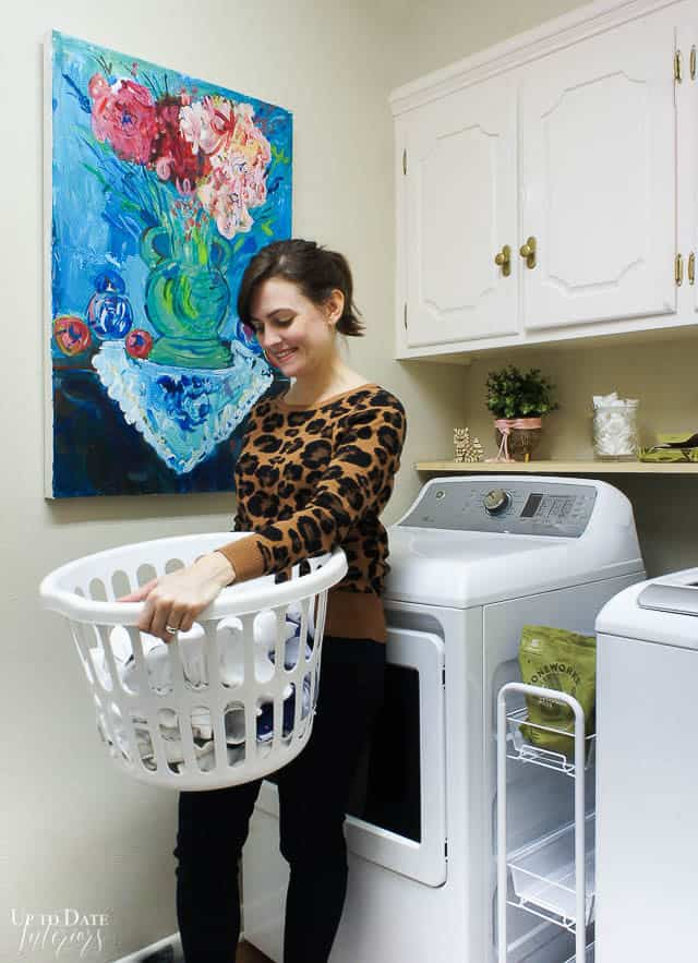 Living green with natural and organic laundry detergent and dryers sheets in a bright laundry room with a woman holding a basket smiling.
