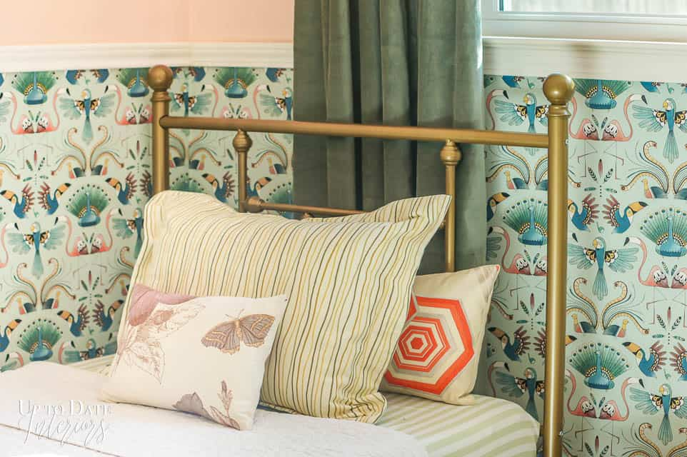 Girls bed featuring globally inspired pillows and bird wallpaper