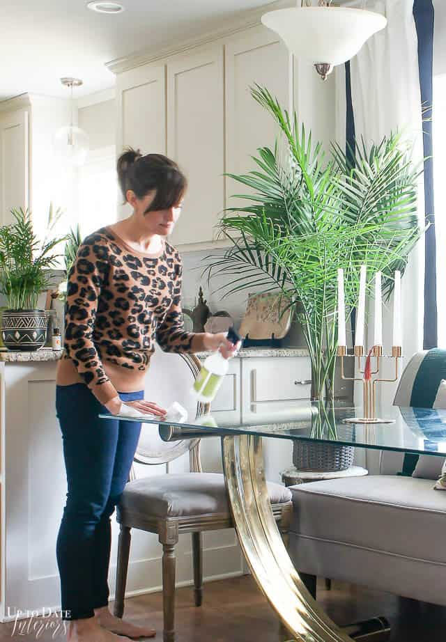 Woman cleaning a glass dining table with a natural household cleaner.
