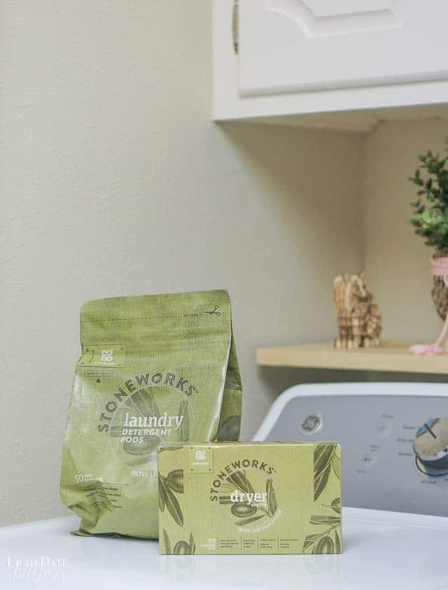 Safe and natural laundry detergent pods and dyers sheets sitting on a dryer.