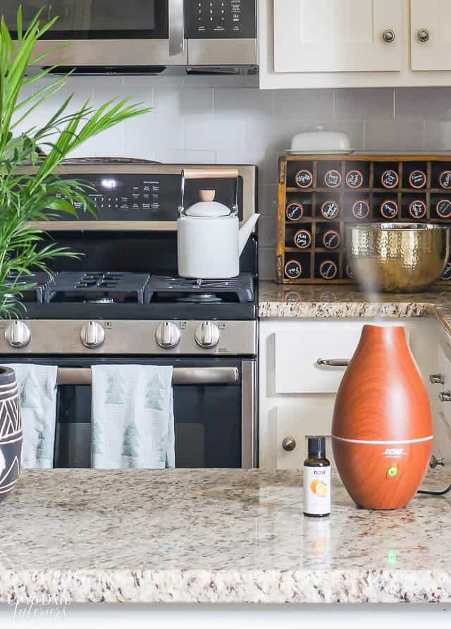 Wood diffuser on kitchen counter with oil essential oil bottle. Bright and white kitchen.