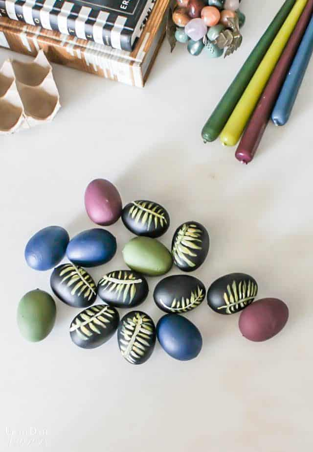 Diy Easter Eggs Botancial Hand Painted Moody Colors with candle sticks and books on a white table