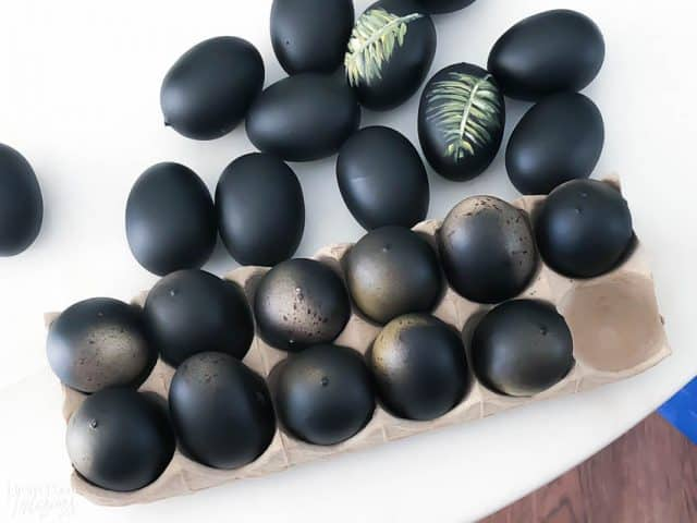 Diy Easter Eggs Botancial Hand Painted black background and green palm leaf on a white table
