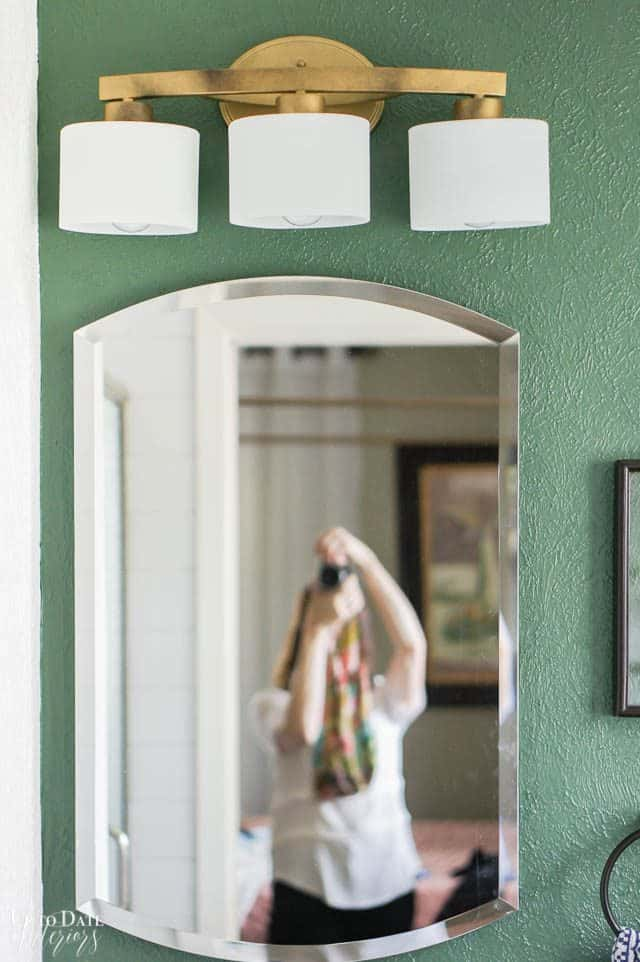 Bathroom Light Diy with gold spray paint on a green bathroom wall and mirrored vanity cabinet