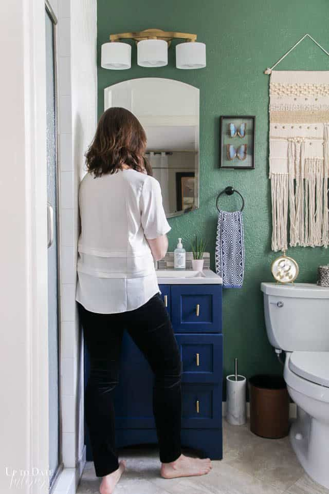 Bathroom Makeover with green and white walls and a blue cabinet. Woman facing the vanity.