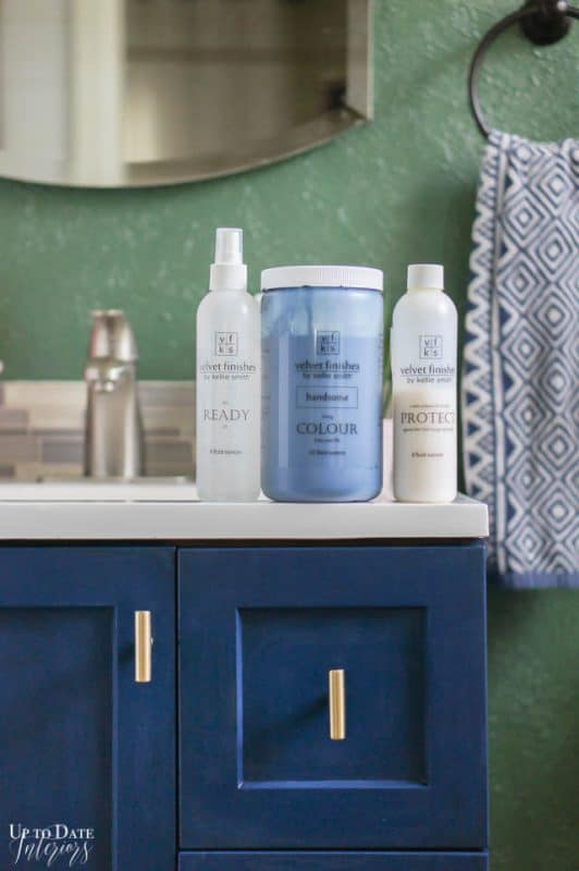 get a Bathroom Makeover On A Budget by painting your existing vanity like a dark blue against a green wall