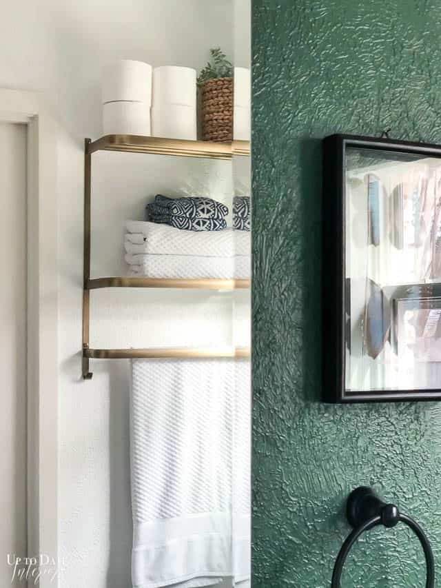 Bathroom Wall Decor Ideas, mirror reflecting gold shelf next to a green wall