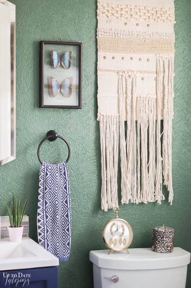 Bathroom Wall Ideas with butterfly art and woven wall hanging on a green wall above the toilet