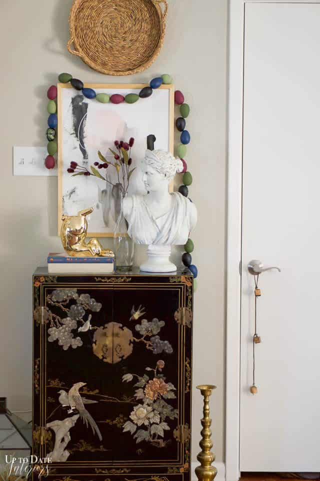 Boho Easter egg garland in moody hues with a woman's bust gold bunny and asian cabinet