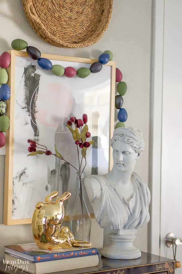 gold bunny on books and DIY egg garland around art with daphne, a ceramic bust