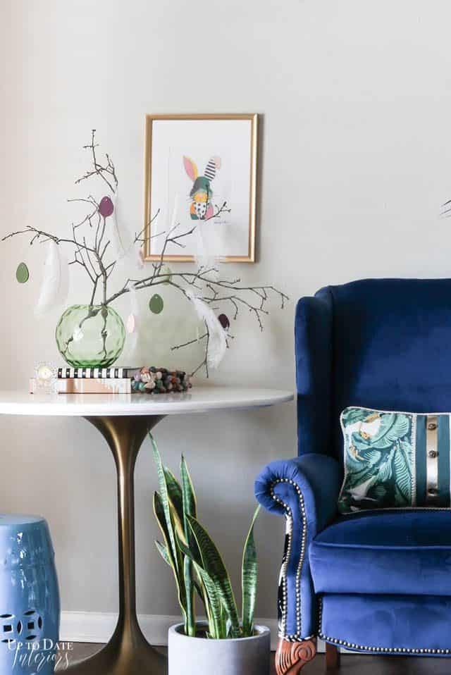 Easter Tree With Diy Clay Eggs next to a marble tulip table, plant, and blue chair.