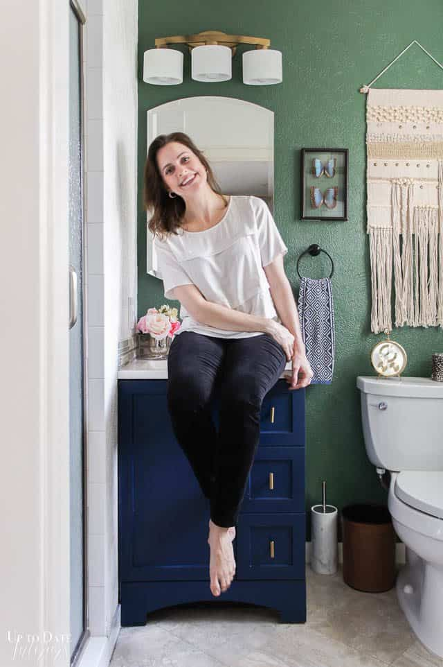 Eclectic Glam Bathroom Makeover with girl sitting on a blue vanity with a gold light fixture and green wall