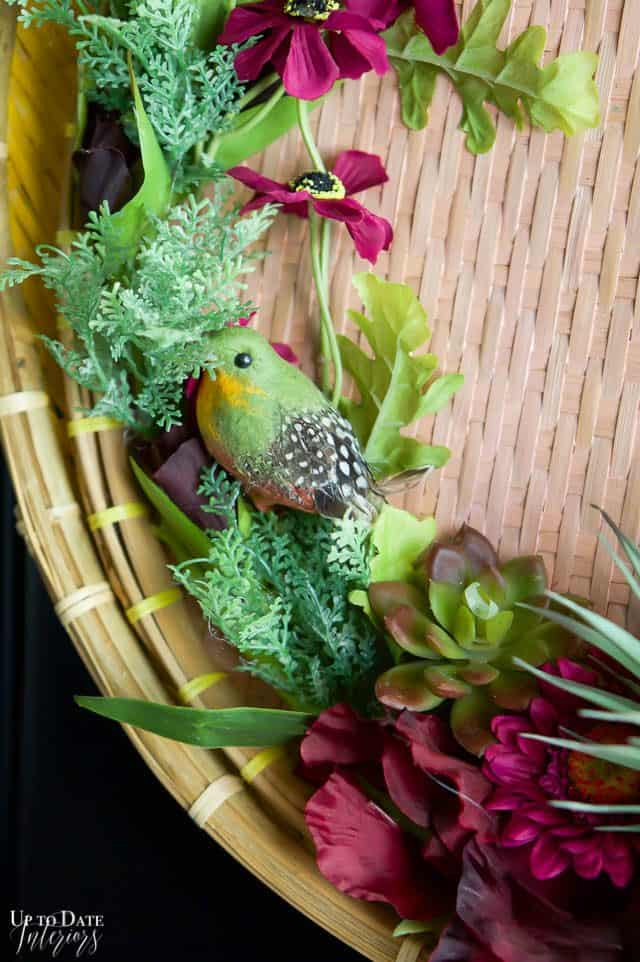 Elegant And Modern Spring Wreath close up with green, pink, black, and purples and a green bird