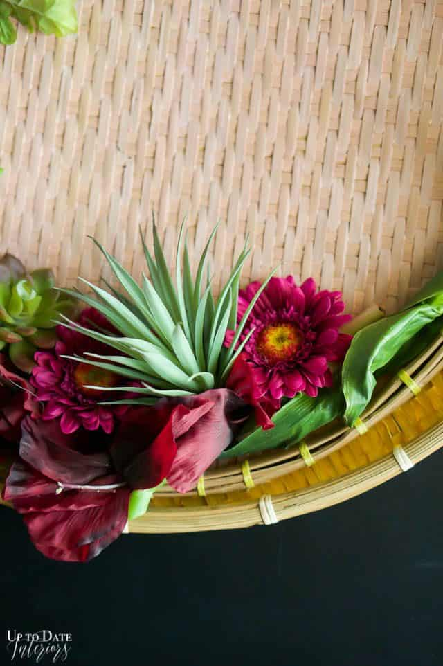Spring Basket wreath close up of purple flowers and succulent on a pink background