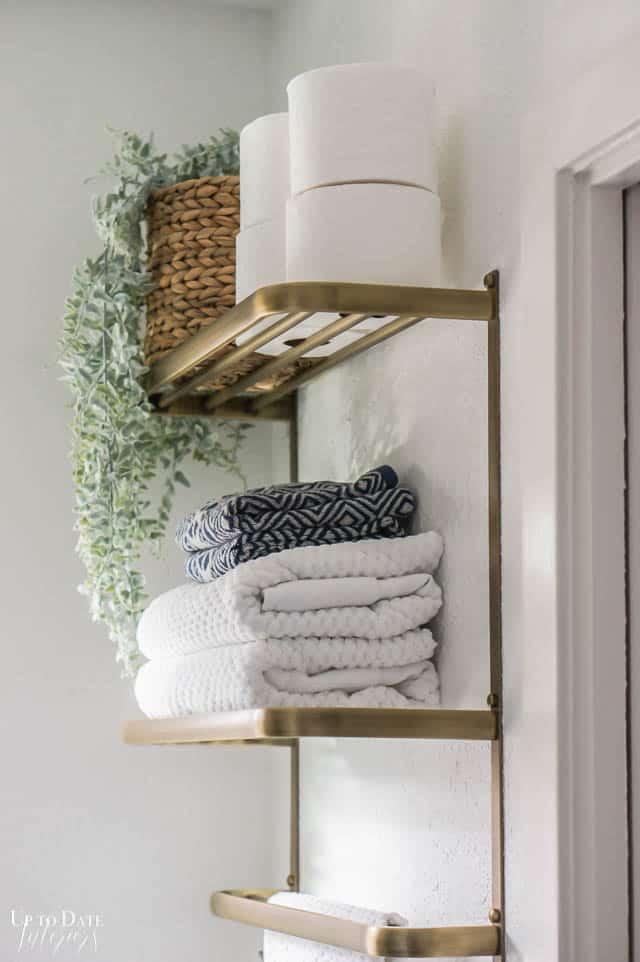 Glam Bathroom Decor with a gold towel bar and shelves housing towels, toilet paper, and a plant on white walls
