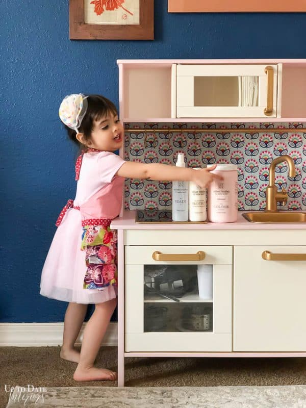 Ikea Play Kitchen Makeover with little girl pointing to Velvet Finishes paint