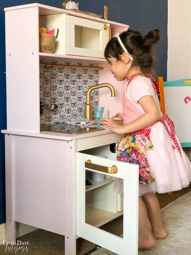 Ikea Play Kitchen hack with pink and patterned back splash. Little girl playing with it.