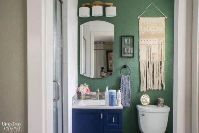 Small Bathroom Makeover with a forest green accent wall and dark blue cabinet