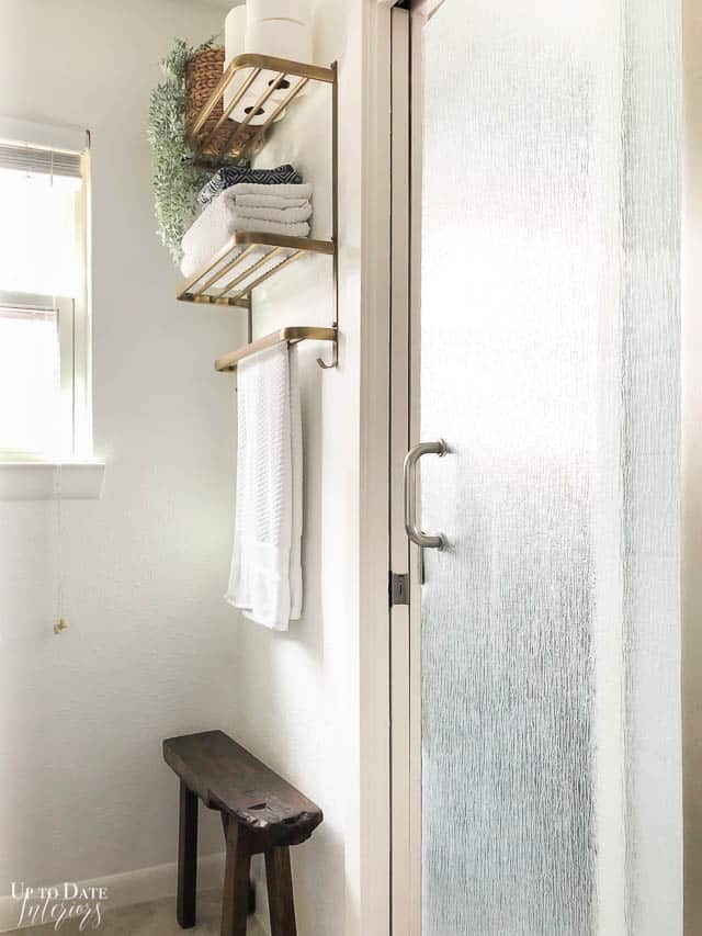 Small Bathroom Makeover On A Tight Budget, view of white walls with a bench and gold towel rack