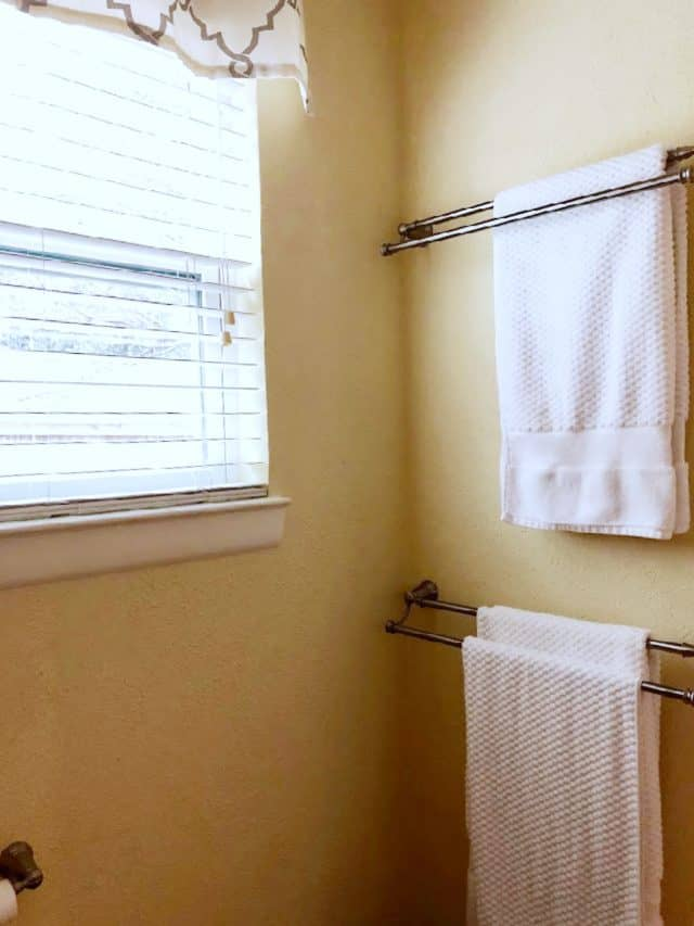 Towel Racks on a yellow wall with window and white towels