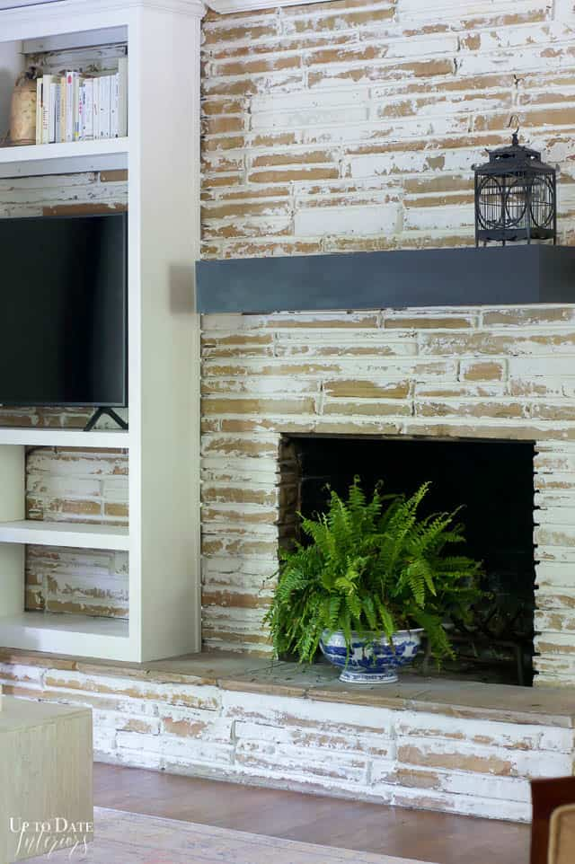 German Smear Mortar Wash Stone Fireplace up close with a dark mantel, bird cage, and plant.