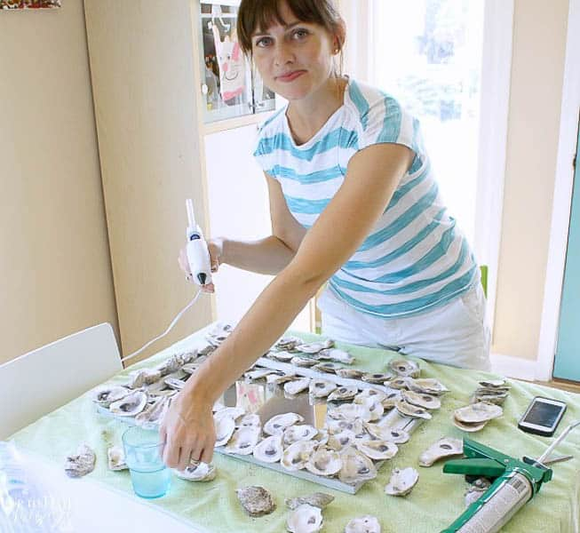 DIY seashell mirror with oyster shells and girl gluing them onto a white mirror in a bright house