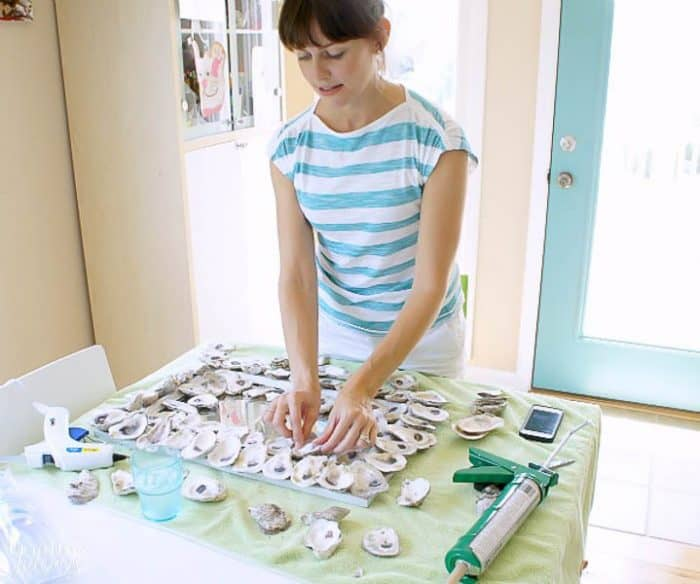 girl gluing oyster shells onto a mirror