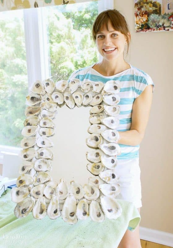 girl holding up diy oyster shell mirror