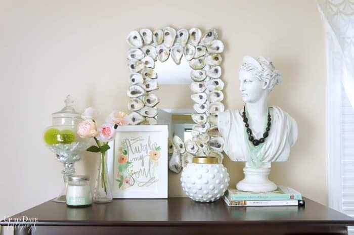 Diy Oyster Shell Mirror with a woman's bust on a dresser